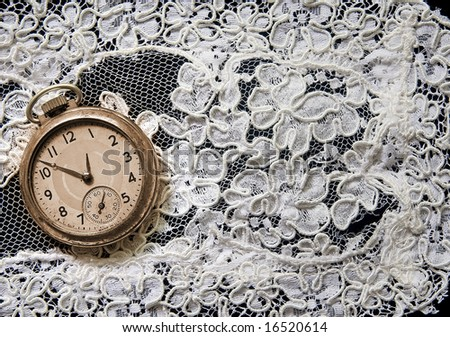 White lace and antique pocket watch on black background - stock photo