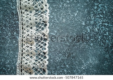 White lace on a dark cement background with copy space for your inscription
