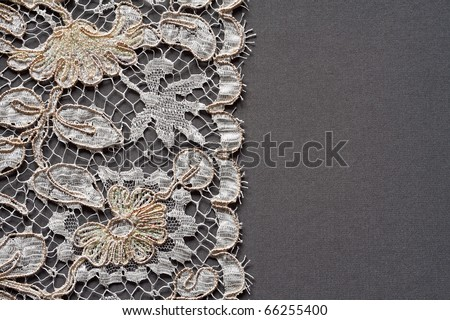 White lace on the dark grey silk background. - stock photo