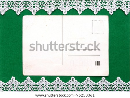 White lace on the green background with blank old postcard