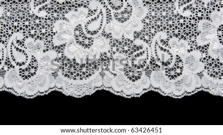 White lace with pattern in the manner of flower on black background - stock photo