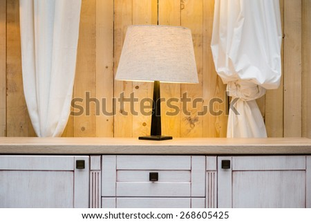 White lamp on the wardrobe with raw wooden wall in the background