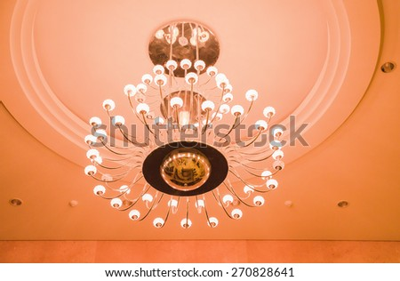 White lamps with brass structure on ceiling in ballroom  - stock photo
