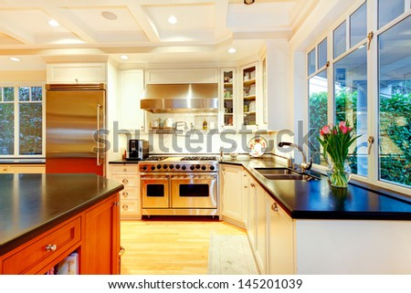 White large luxury kitchen with huge stove and refrigerator. - stock photo