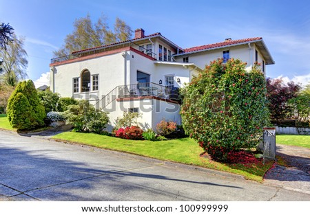 White large white Spanish style house with back yard. - stock photo