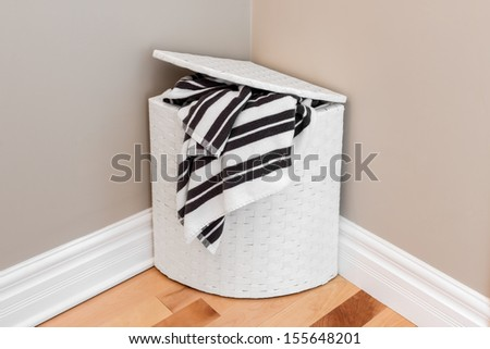White laundry basket with striped towels in the room corner. - stock photo