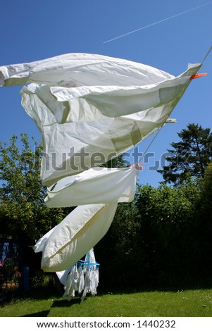 White laundry drying on a hot and windy summer day - stock photo