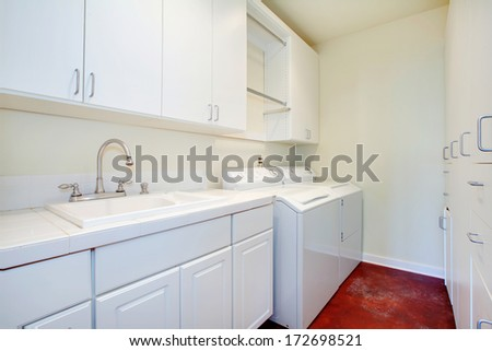 White laundry room with a red floor and white wooden storage combination - stock photo