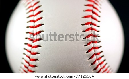 white leather baseball with red stitching on black background - stock photo