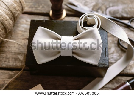 White leather bow tie and black gift box with crafts and tobacco pipe on wooden table, close up