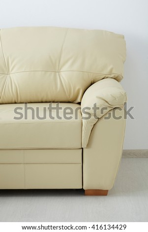 White leather sofa isolated against the wall