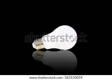 white LED light bulb isolated on black background with reflection - stock photo