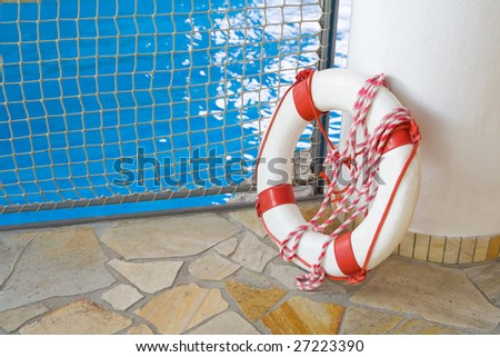 White life buoy on floor by swimming pool - stock photo