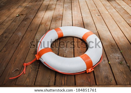 White lifebuoy with red stripes and rope on weathered wooden wall in port - stock photo
