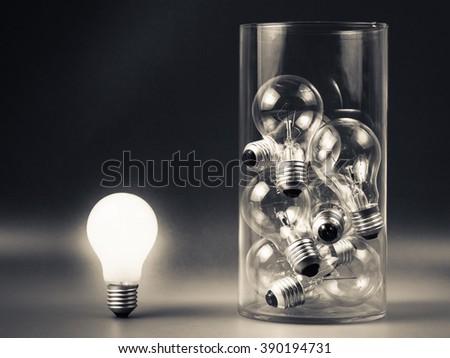 White light bulb glowing outside the bottle - stock photo