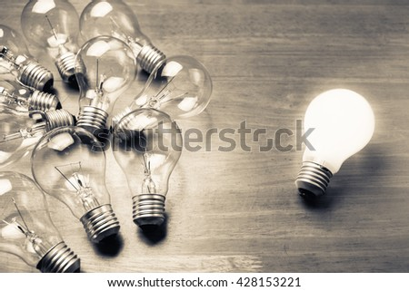 White light bulb glowing separate from others - stock photo