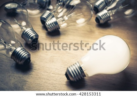 White light bulb glowing separate from the others - stock photo