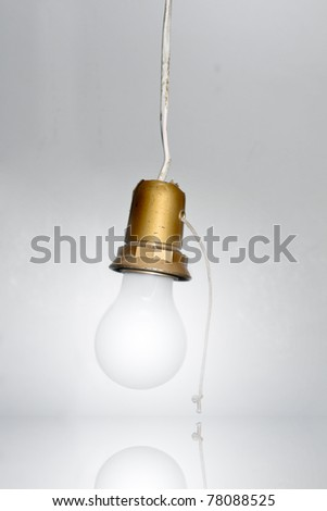 White light bulb turned on, isolated on white backgournd and reflecting on a mirror. - stock photo