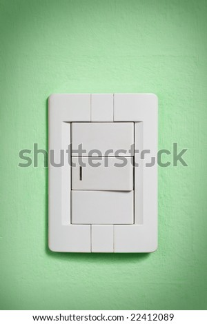White light switch against a green wall. - stock photo