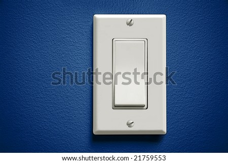 White light switch against blue wall - stock photo