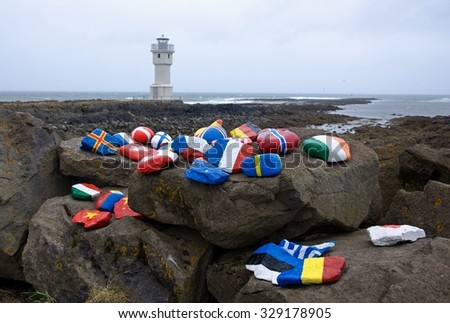 White lighthouse at the port of Akranes with national flags painted on rock, Iceland - stock photo