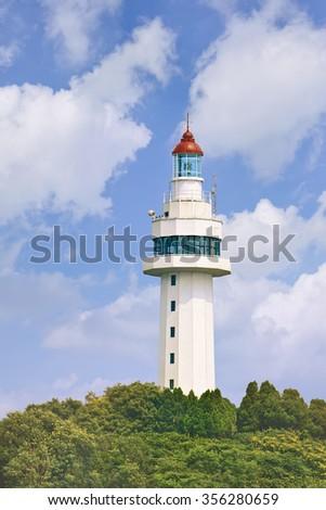 White lighthouse on a lush green hill, Yantai, China - stock photo