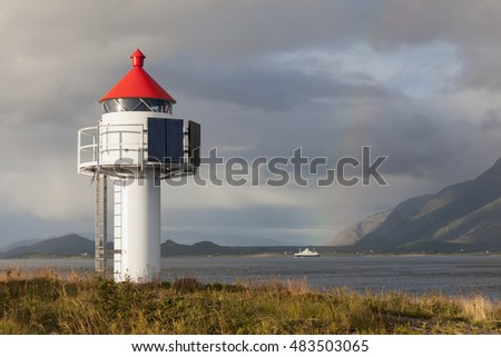 White lighthouse with red roof and solar panels at Norwegian coast at autumn; with mountains, rainbow and local ferry in background