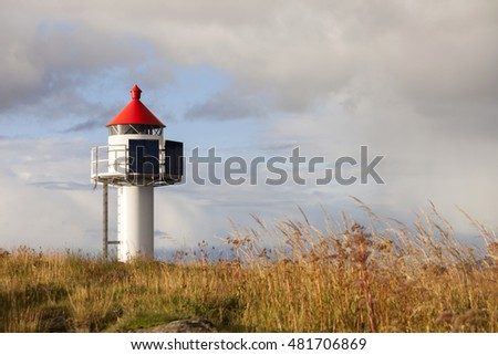 White lighthouse with red roof and solar panels in long grass at autumn