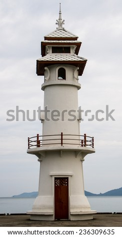 White lighthouse with sea view background. - stock photo