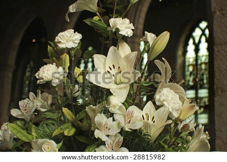 white lilies in the church by stained glass - stock photo