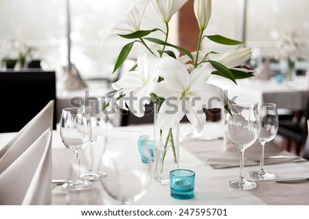 White Lily flowers bridal decoration in glass vase on table settings, empty wineglasses and candles waiting for guests in restaurant interior, Poland, horizontal orientation, nobody. - stock photo