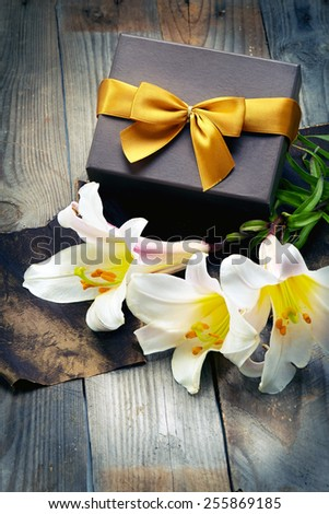 white lily with box on wooden table - stock photo
