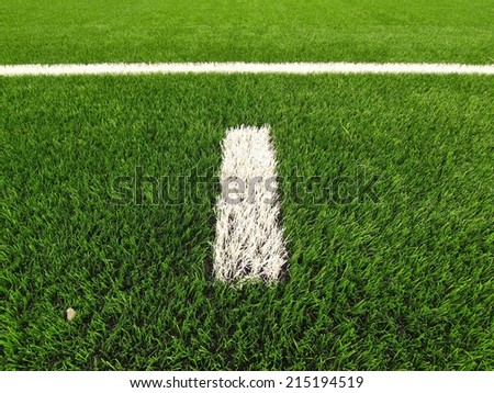 White line marks painted on artificial green turf background. Winter football playground with plastic grass. - stock photo