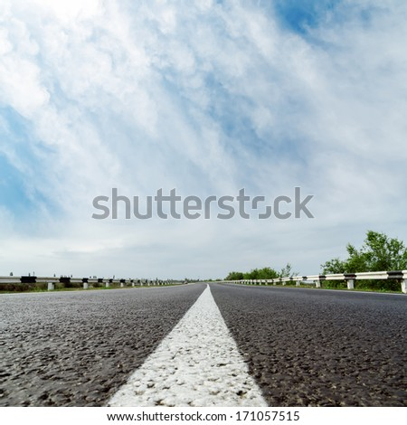 white line on asphalt road and clouds over it - stock photo