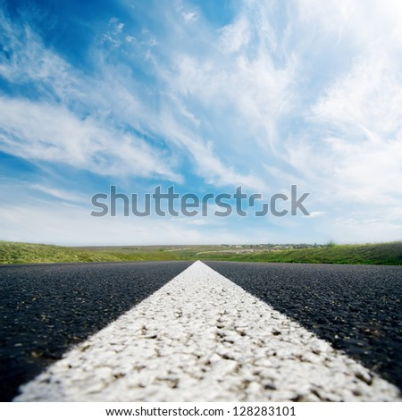 white line on asphalt road close up and cloudy sky - stock photo