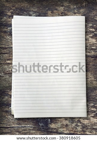 white lined sheet of notepad paper on old wooden - stock photo