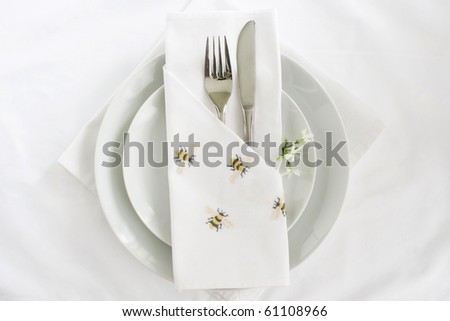 White linen place setting with knife and fork and embroidered bee napkin - stock photo