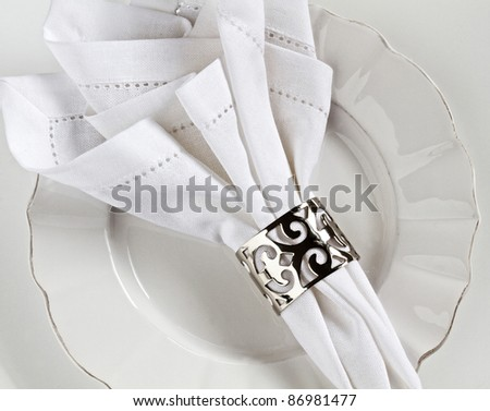 White linen table place setting with silver serviette ring - stock photo
