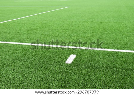 White lines on football playground. Detail of lines in a field. Plastic grass and finely ground black rubber.