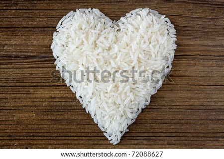 White long uncooked rice on old wooden board - stock photo