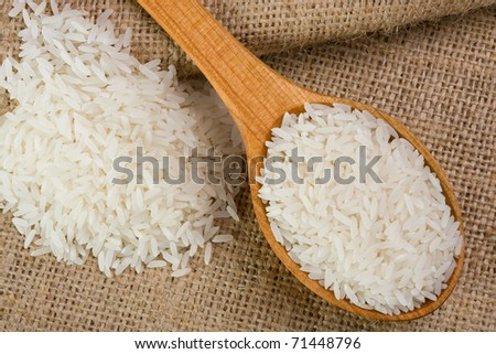 White long uncooked rice on wooden spoon - stock photo