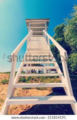 white lookout tower at a beach on background blue sky - stock photo