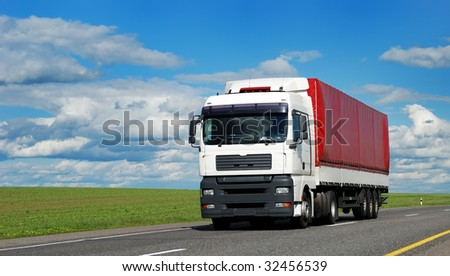 white lorry with red trailer on the highway over blue cloudy sky