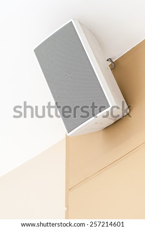 White loudspeaker is hanging on the wall of shopping mall. - stock photo