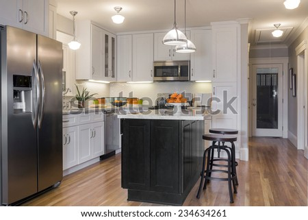 White luxurious Kitchen in Modern Home with white Marble counter tops, wooden floor, bar chairs, deep sink and all new stainless steel appliances. - stock photo