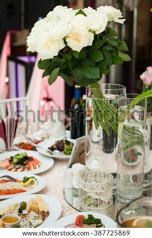 White, luxury wedding reception table arrangement with flowers centerpiece - stock photo