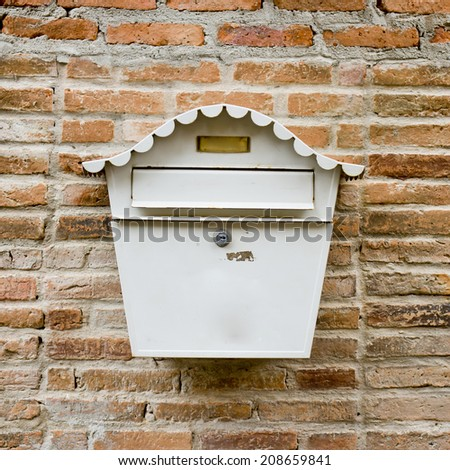 White Mail Box in Front of wall - stock photo