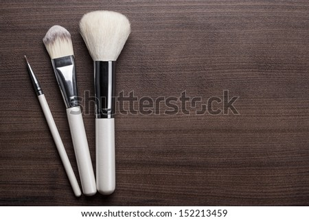 white make-up brushes on brown wooden background - stock photo