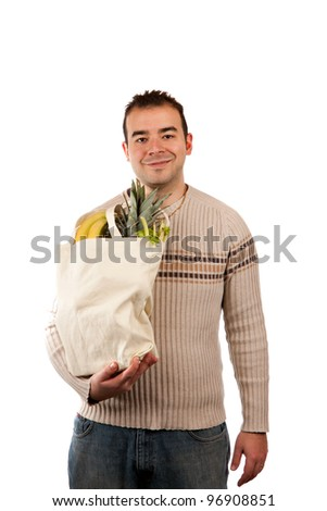 White male grocery shopper smiling while holding a canvas bag full of fresh food items. - stock photo
