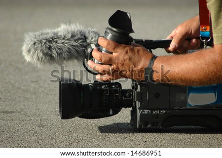 White male hands of a caucasian man with his portable big tv camera working on the road filming a movie about a sport event outdoors - stock photo